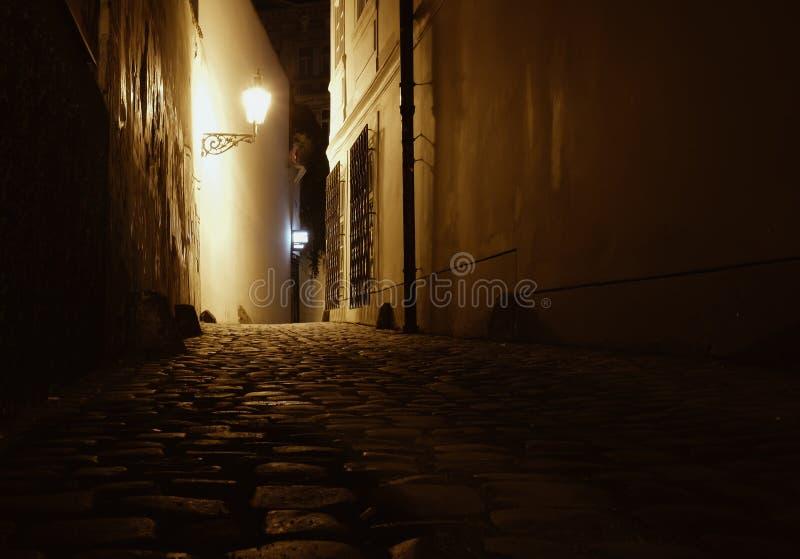 有古老铺路石路twiligh的老布拉格狭窄街道 库存照片