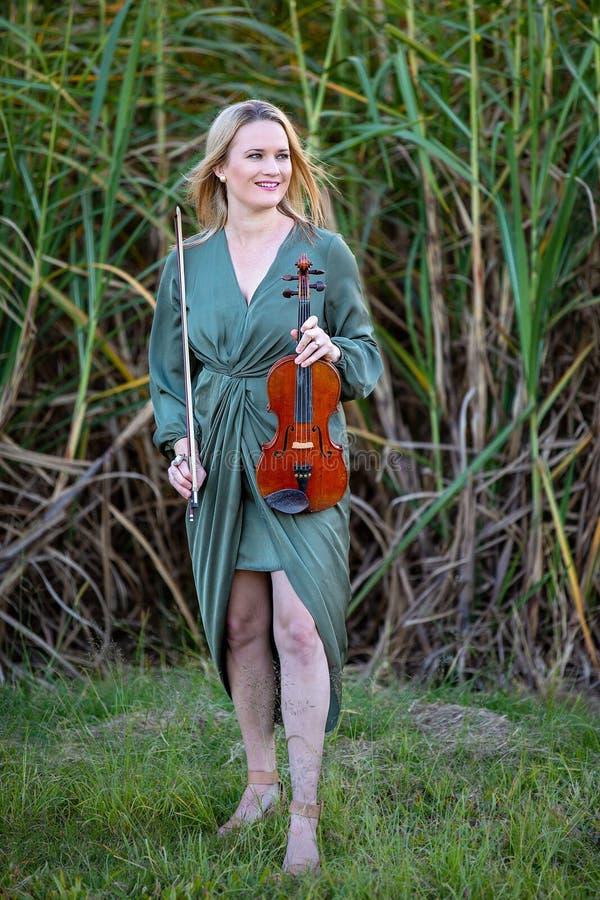 有古色古香的仪器的美丽的女性小提琴手在日落 库存照片