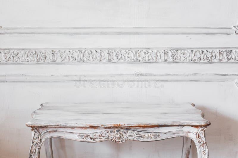 有古色古香的时髦的淡色的桌的客厅在豪华白色墙壁设计浅浮雕灰泥造型roccoco 免版税库存照片