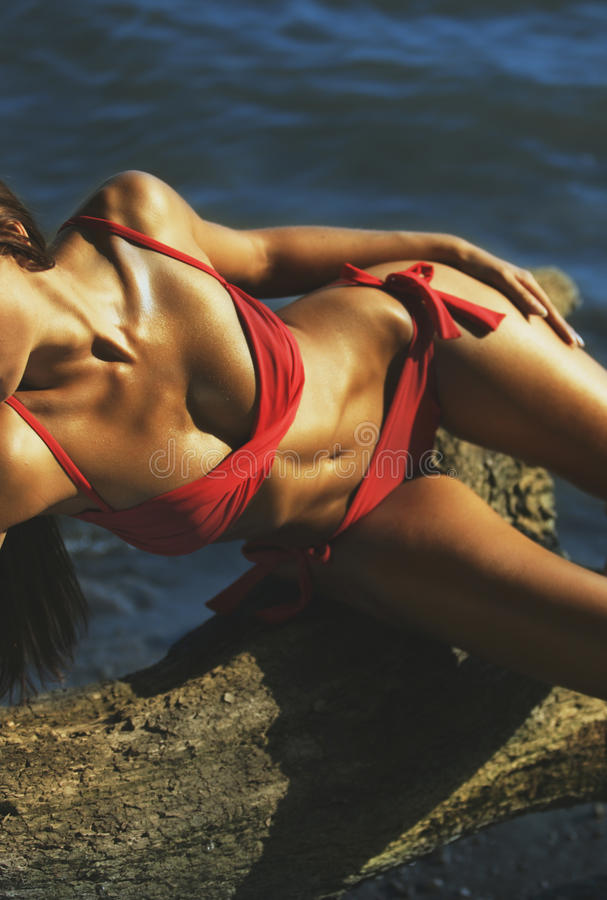 有古铜棕褐色的美丽的妇女在海边,与油和红色 免版税库存图片