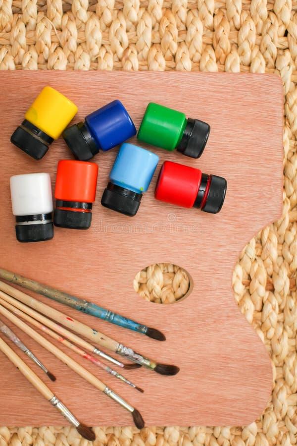 有另外油漆的木艺术在柳条背景,从上面的看法的调色板和刷子 免版税库存图片