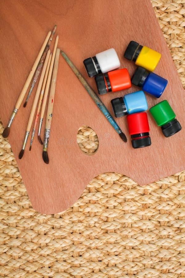 有另外油漆的木艺术在柳条背景,从上面的看法的调色板和刷子 免版税图库摄影