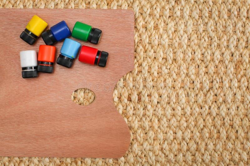 有另外油漆的木艺术调色板在柳条背景,从上面的看法 免版税库存照片