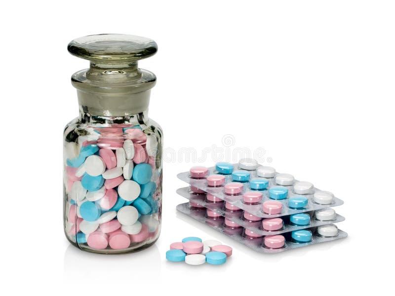有另外颜色药片的塑料装箱和玻璃小瓶。 免版税库存照片