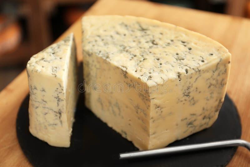 有可口乳酪片断的板岩板材  库存图片