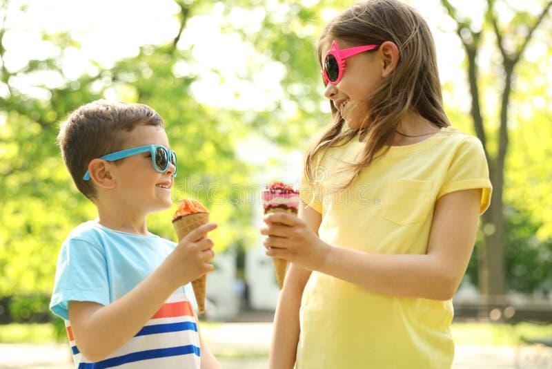 有可口冰淇淋的逗人喜爱的小孩 库存照片