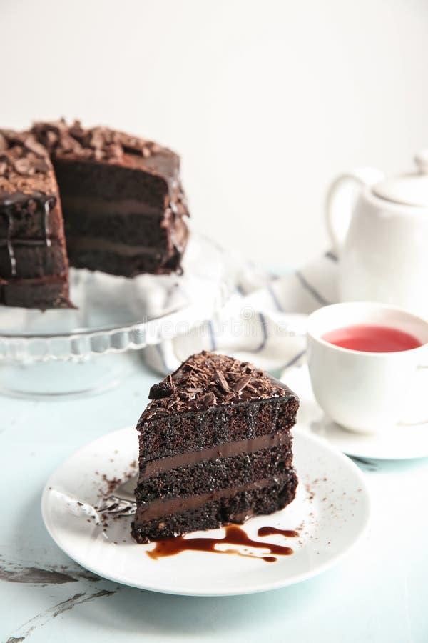 有可口巧克力蛋糕片断和茶的板材在轻的桌上的 库存照片