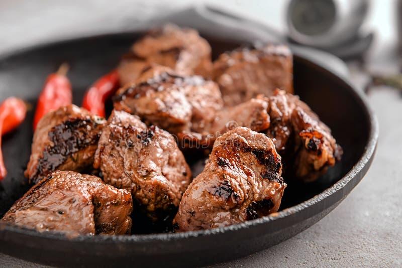 有可口烤肉串的煎锅在桌,特写镜头上 免版税库存图片