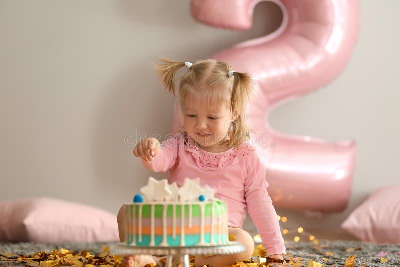 有可口蛋糕的逗人喜爱的女孩坐地毯在为生日宴会装饰的屋子里 免版税图库摄影