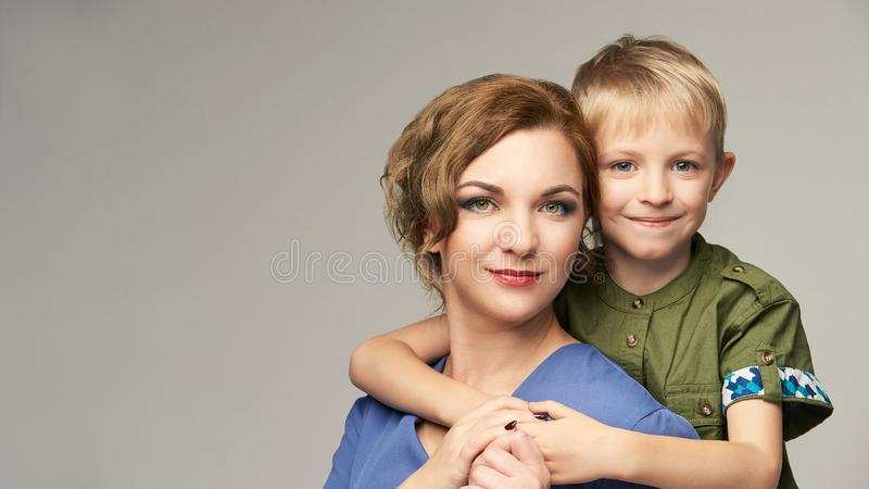 有可爱宝贝男孩的俏丽的成熟妈妈 一起肩扛画象 母亲父母拥抱 免版税库存图片