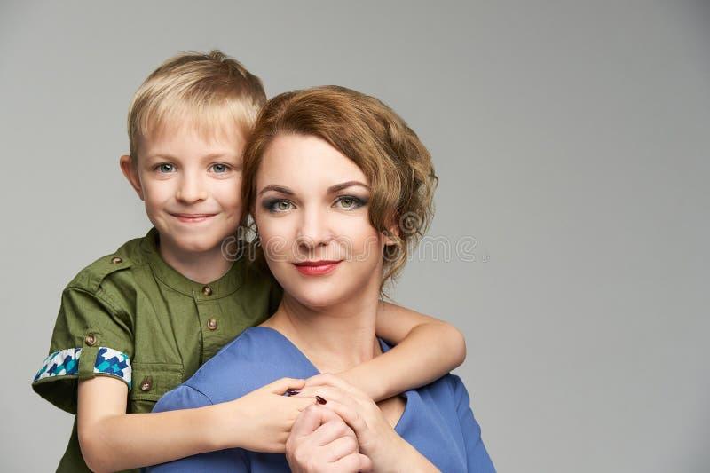 有可爱宝贝男孩的俏丽的成熟妈妈 一起肩扛画象 母亲父母拥抱 库存照片