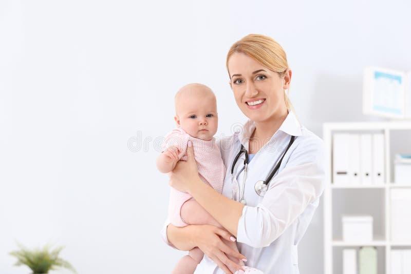 有可爱宝贝的儿童的医生在医院 库存照片
