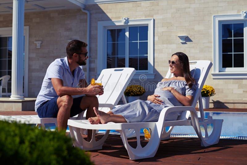 有可爱的夫妇在现代房子前面的休息有水池的 免版税图库摄影