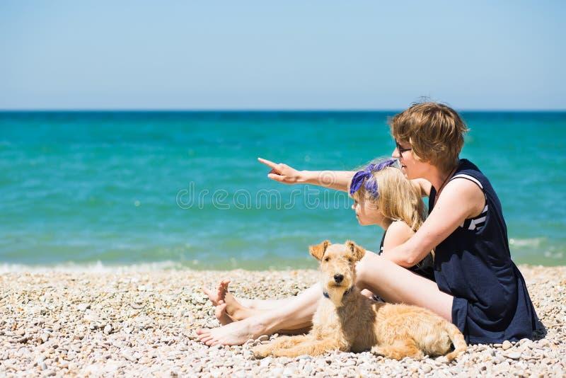 有可爱的女儿和狗的美丽的妇女在海滩 免版税图库摄影