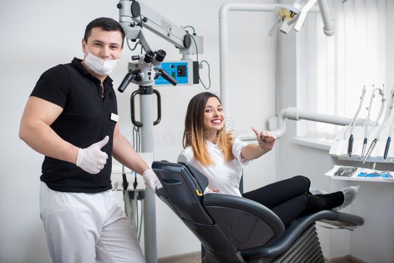 有可爱的女性患者的英俊的男性牙医在现代牙齿诊所的治疗以后 免版税库存照片