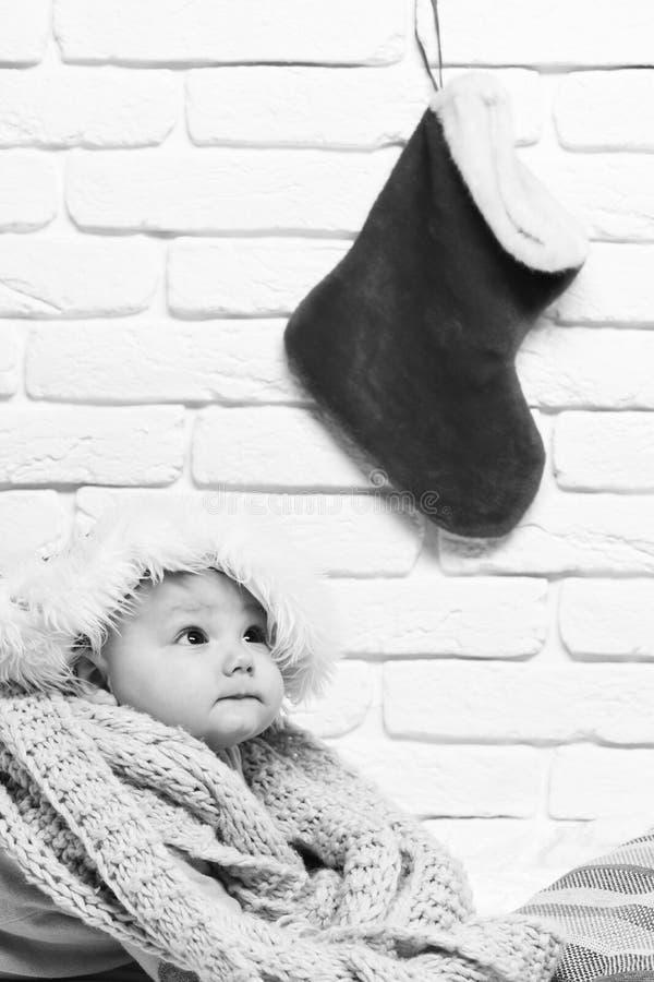 有可爱的好奇面孔的小男婴在新年帽子和被编织的围巾的黄色毛线衣有圣诞节或xmas的 库存照片