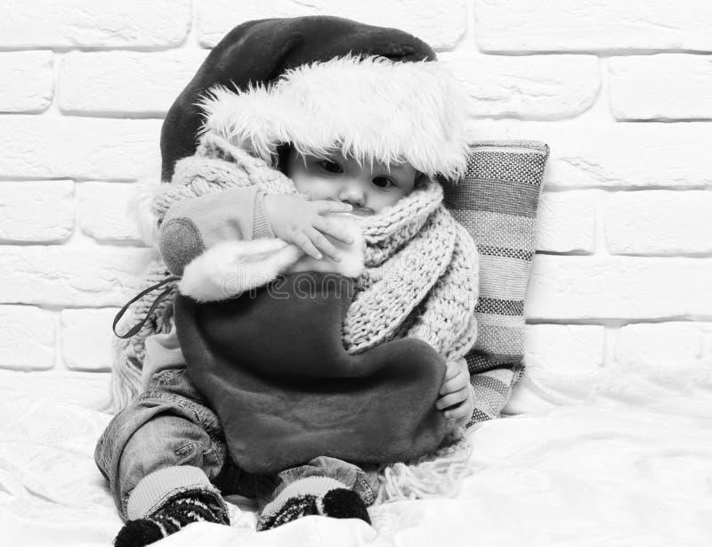 有可爱的好奇面孔的小男婴在有钝汉的红色毛线衣在新年帽子围巾和圣诞节或者xmas长袜 库存图片