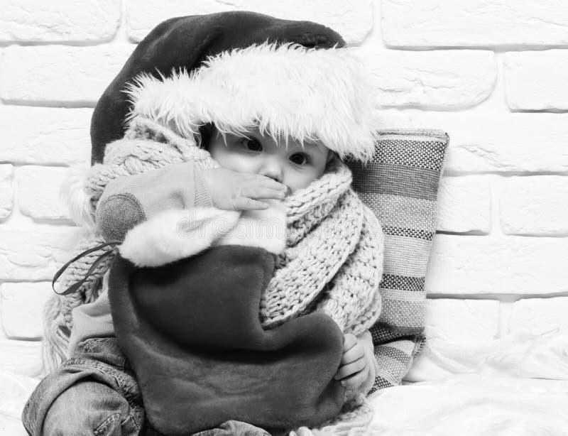 有可爱的好奇面孔的小男婴在有钝汉的红色毛线衣在新年帽子围巾和圣诞节或者xmas长袜 免版税库存图片