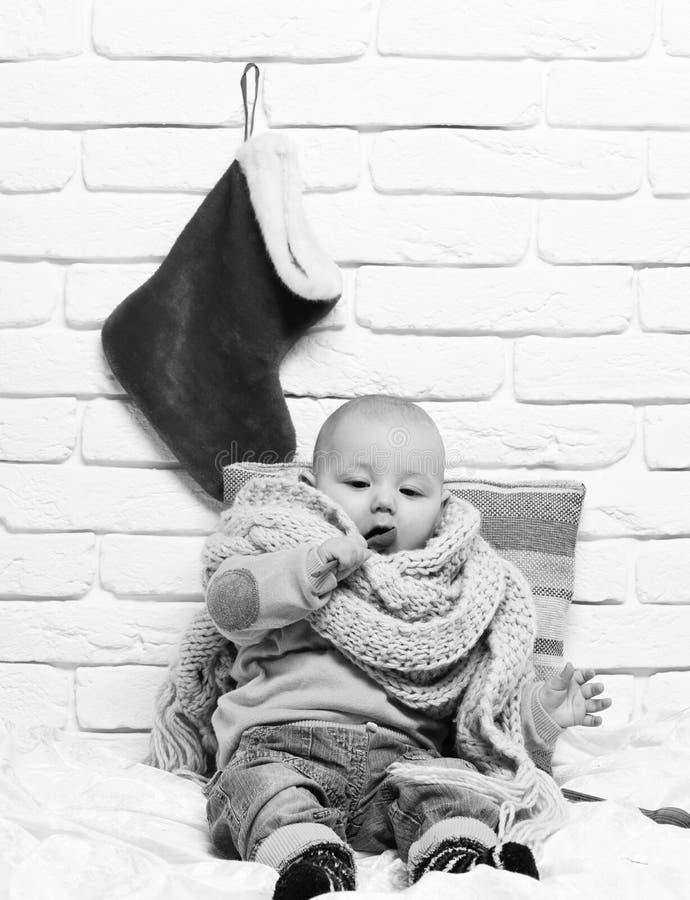有可爱的好奇面孔的小男婴在黄色毛线衣和被编织的围巾有圣诞节的或xmas长袜或者起动  库存照片