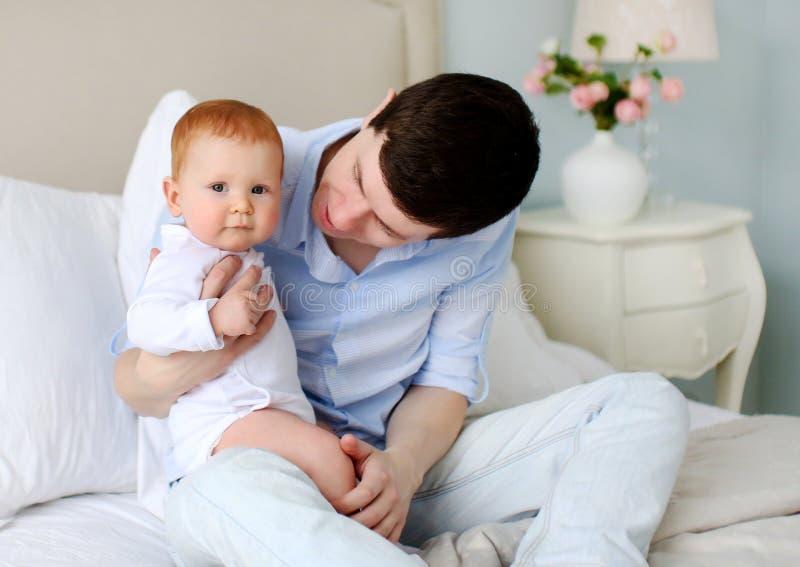 有可爱的婴孩的一个愉快的父亲在卧室 爸爸和女儿 库存照片
