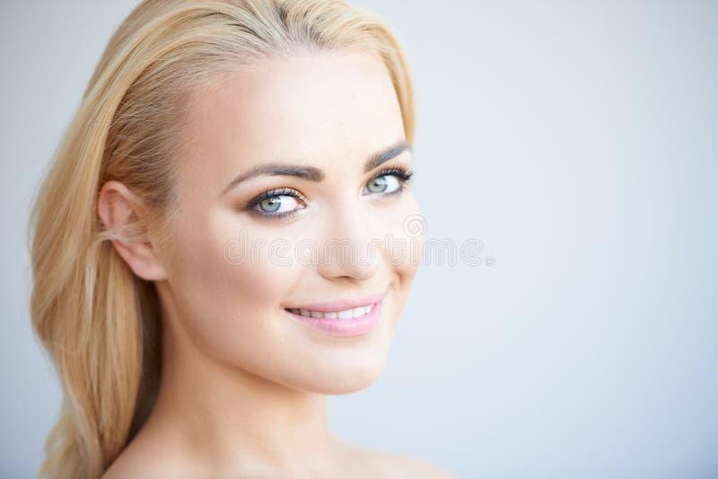有可爱的微笑的美丽的白肤金发的妇女 免版税库存图片