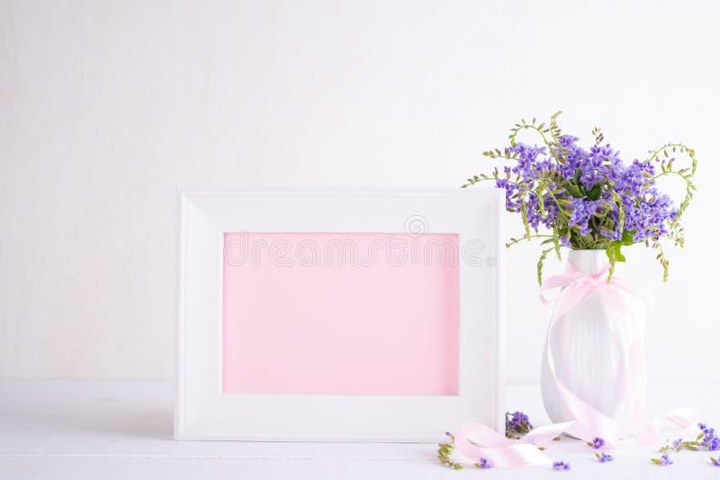 有可爱的紫色花的白色相框在白色木桌上的花瓶 库存图片
