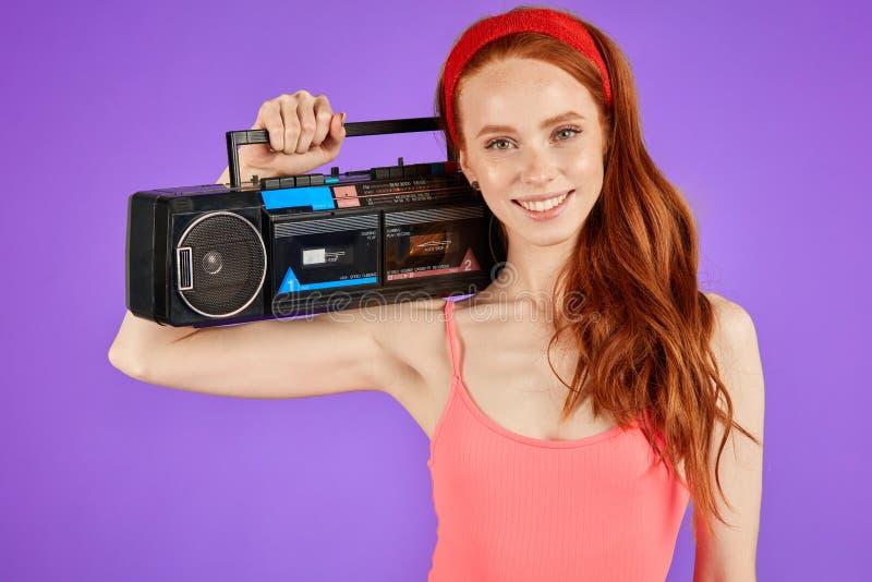有可爱的雀斑的红发女孩,拿着她的肩膀的便携式的卡式磁带播放机 库存图片