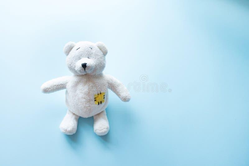 有可看见的上身的逗人喜爱的白色玩具熊儿童玩具和在蓝色背景的开放胳膊与拷贝空间 免版税图库摄影