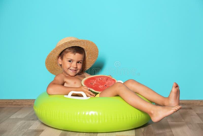 有可膨胀的圆环和西瓜的逗人喜爱的小男孩 免版税库存照片