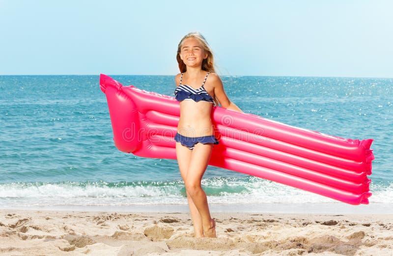 有可膨胀的床垫的愉快的女孩在白色海滩 免版税库存图片