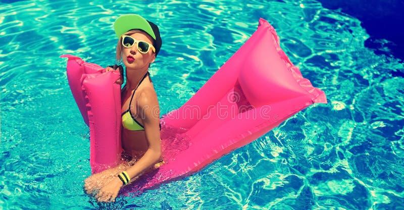 有可膨胀的床垫的魅力女孩在水池热的夏天同水准 免版税图库摄影