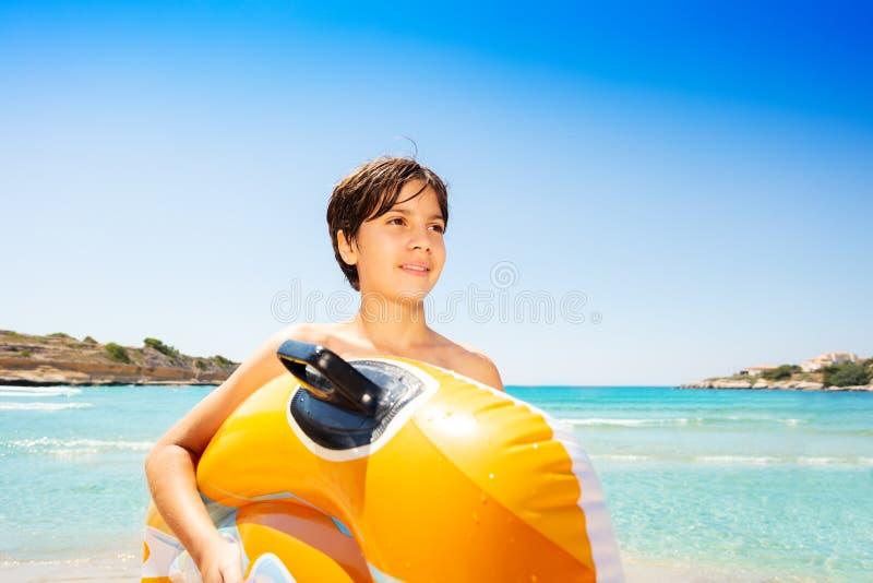 有可膨胀的浮游物的愉快的男孩在热带海滩 免版税库存照片
