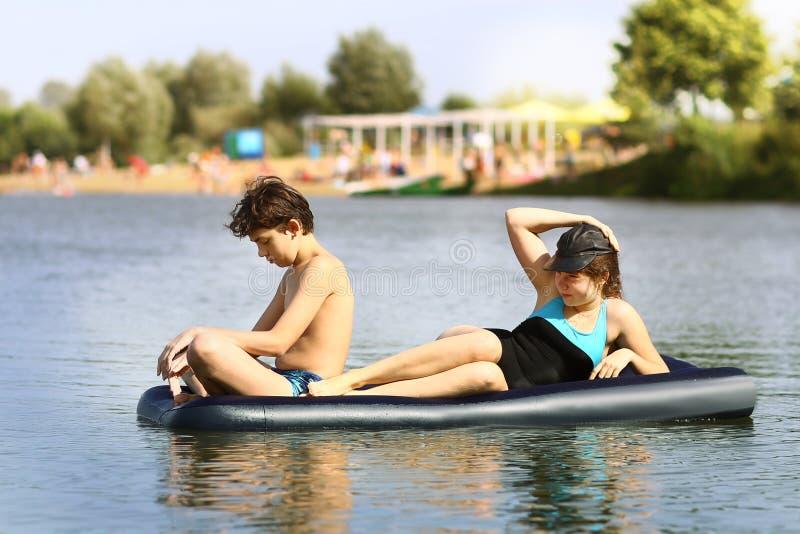 有可膨胀的matrass的兄弟姐妹兄弟和姐妹在沙子海滩背景的湖游泳 免版税库存照片