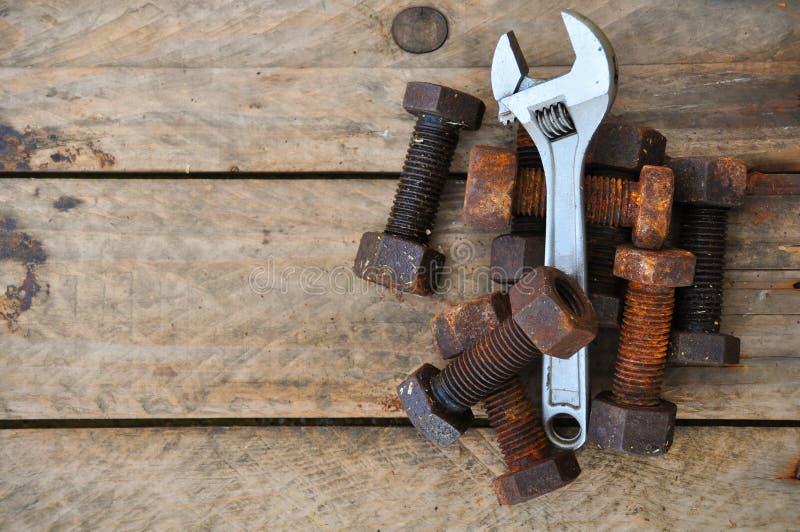有可调扳手工具的老螺栓在木背景 库存图片