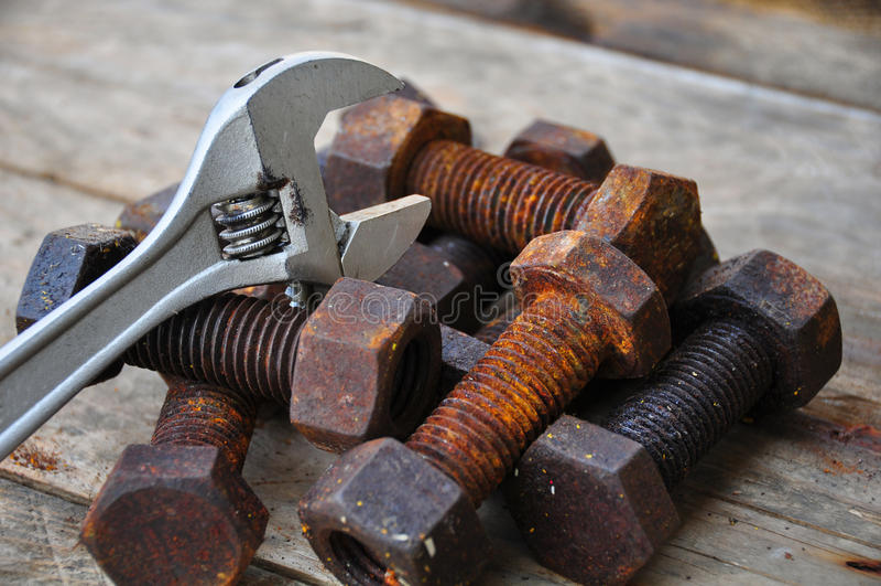 有可调扳手工具的老螺栓在木背景 免版税图库摄影