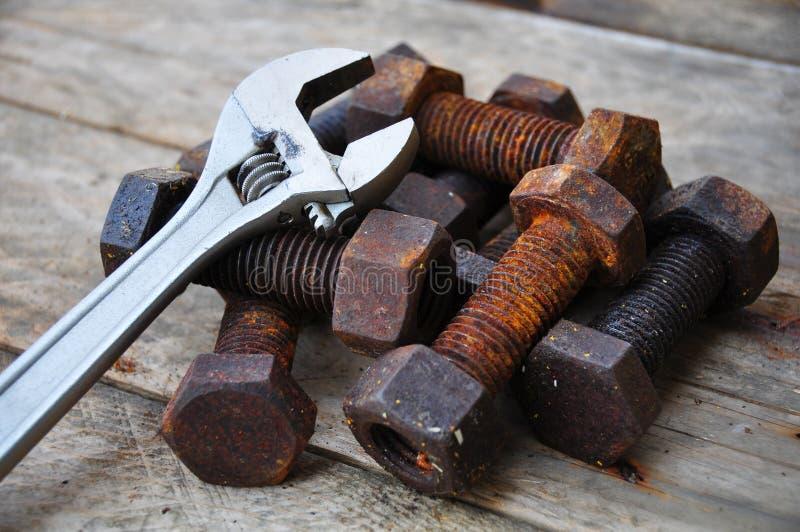 有可调扳手工具的老螺栓在木背景 图库摄影
