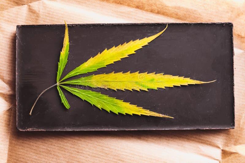 有可食的黑暗的巧克力块的大麻叶子和大麻果仁巧克力有在白色背景的ganja顶视图 免版税库存照片