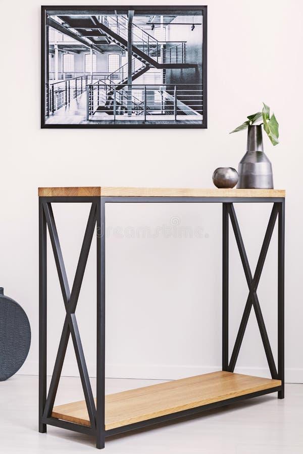 有叶子和蜡烛身分的花瓶在与金属腿的时髦的现代桌上 在墙壁上的工业海报 库存图片