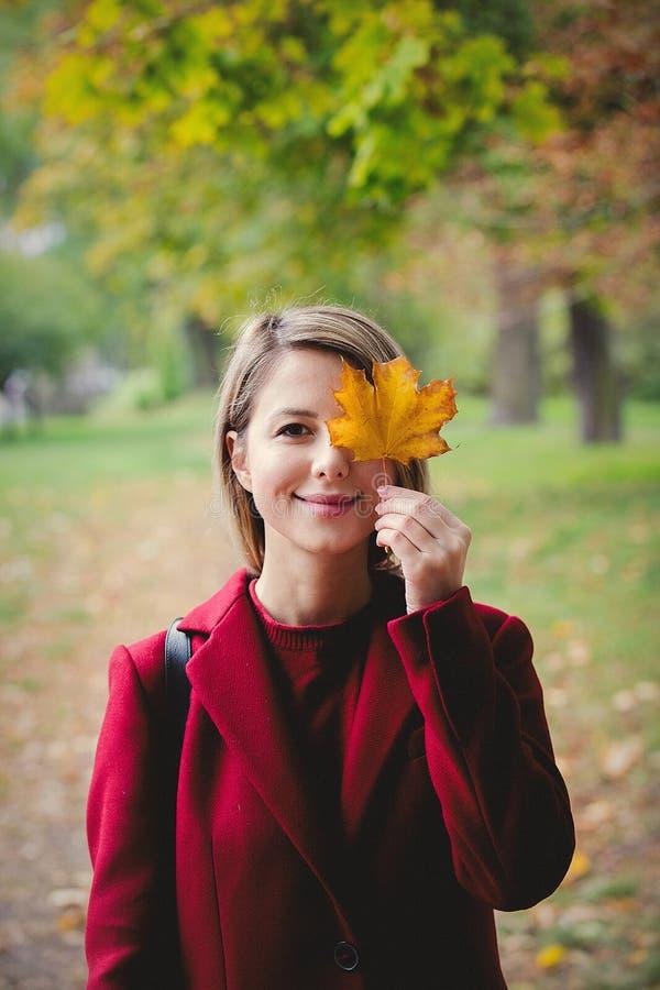 有叶子的年轻样式女孩在公园胡同 免版税库存照片