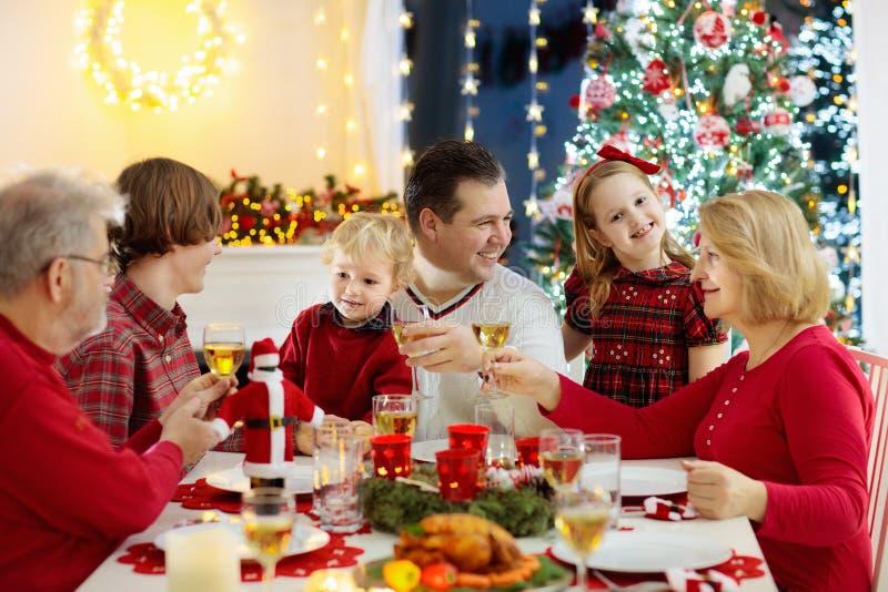 有吃圣诞晚餐的孩子的家庭在壁炉和装饰的Xmas树 父母、祖父母和孩子在欢乐膳食 库存图片