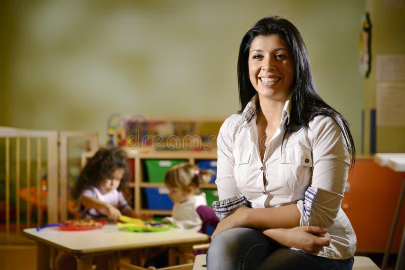 有吃在幼稚园的子项的愉快的教师 免版税图库摄影