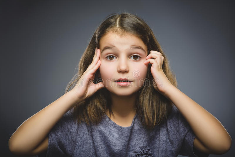 有吃惊的表示的小女孩,当站立反对灰色背景时 库存图片