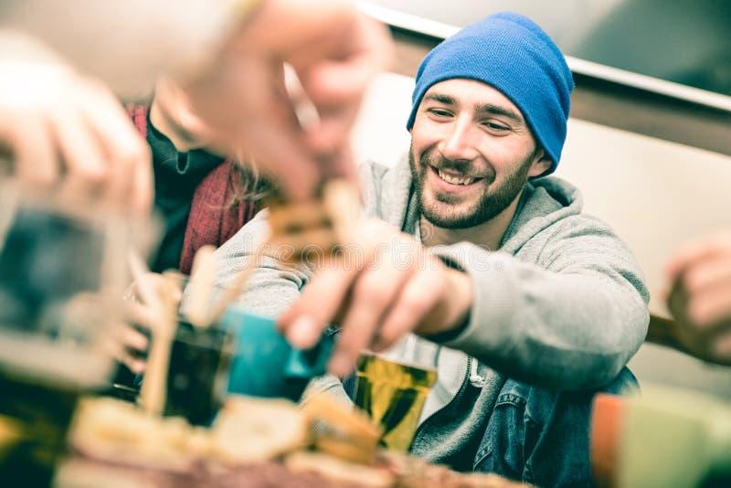 有吃手抓食物和喝啤酒的朋友的愉快的人 库存照片