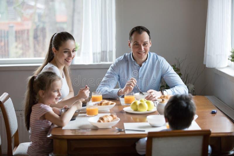 有吃早晨早餐的孩子的幸福家庭在厨房 免版税库存图片