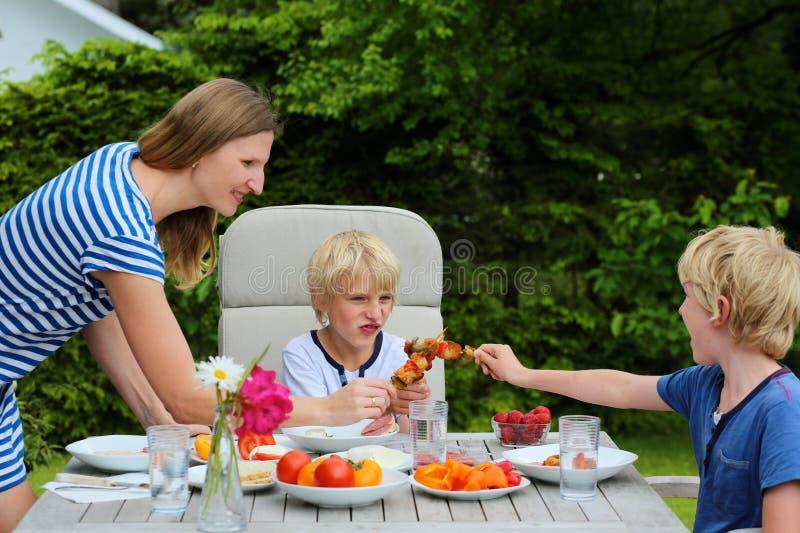 有吃的孩子的母亲户外 库存照片