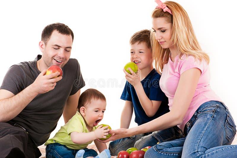 有吃苹果的孩子的白种人家庭 库存照片