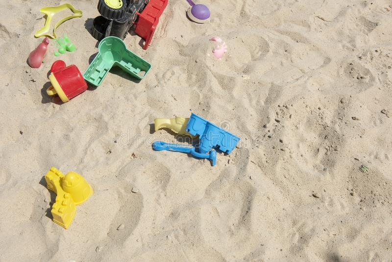 有各种各样的形状和种类的五颜六色的塑料玩具在沙子箱子剩下未看管在手段 库存图片