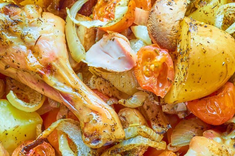 有各种各样的菜的被烘烤的烧鸡腿 免版税库存图片