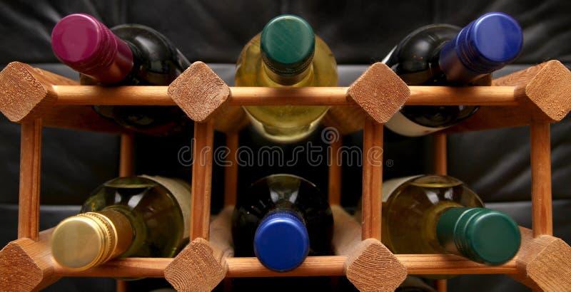 有各种各样的颜色瓶的木酒机架在黑暗的backgrou冠上 图库摄影