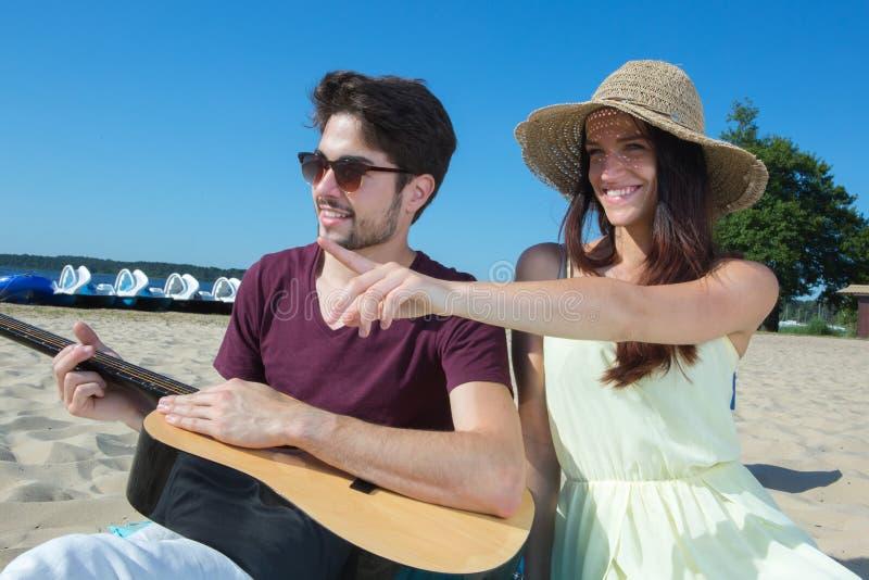 有吉他和女朋友的年轻人海滩的 图库摄影
